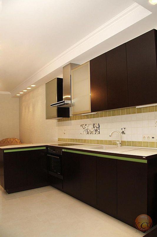 Современная модель кухни выполнена без ручек в итальянском стиле. Фасады фанерованы шпоном венге и покрыты тремя слоями матового лака.
